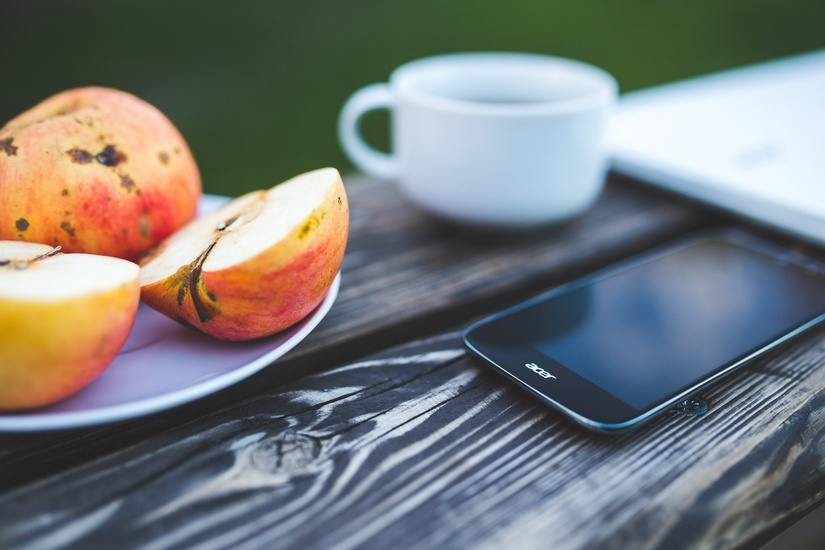 Telefon, äpplen, kaffe på bord.